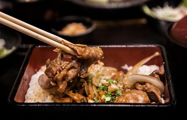 クローズアップ玉ねぎとニンニクの豚肉を盛り合わせて木製の箸
