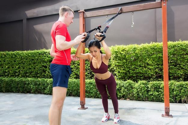 伸縮性のあるロープとバーを備えた屋外公園でのフィットネスコーチングのトレーニング