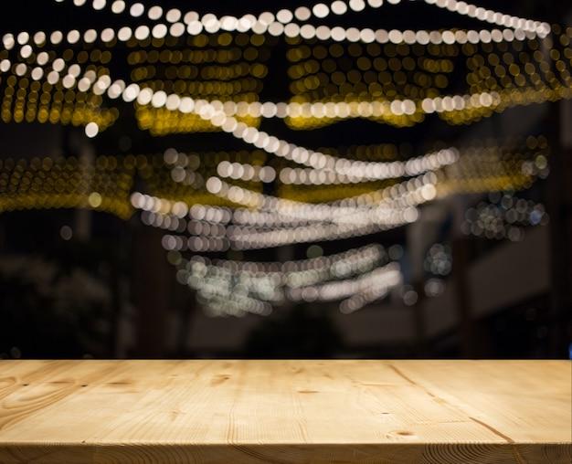 夜の光の背景を持つ木製テーブルトップカウンター