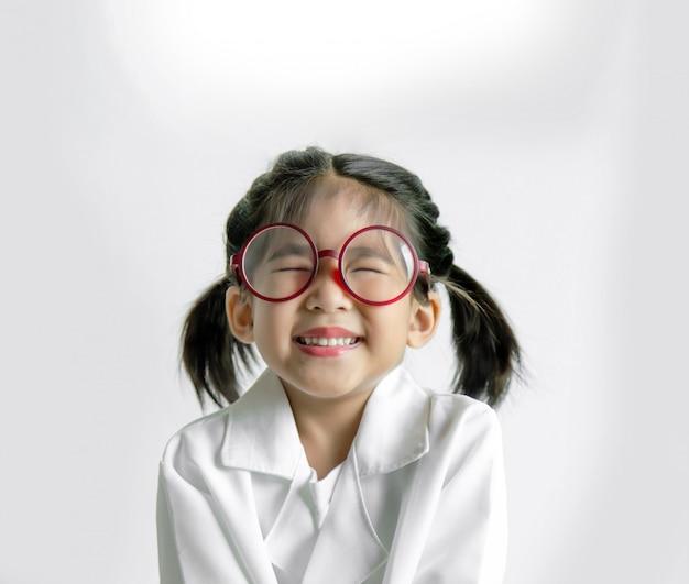 Азиатский малыш в белой форме, как доктор или изобретатель счастливое действие со стеклом