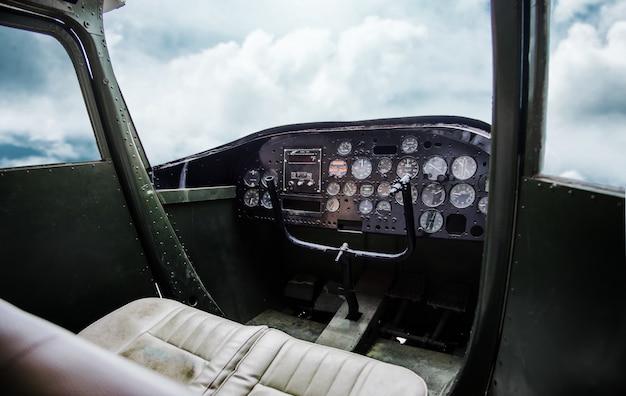 曇り空が付いている飛行機の古いコックピットのインテリア