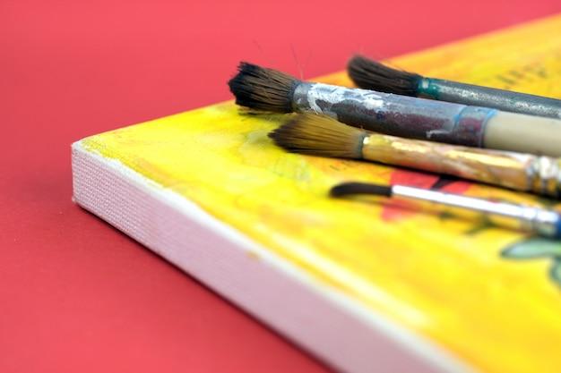 キャンバスのデザインにアーティストのアクリル絵の具と絵筆