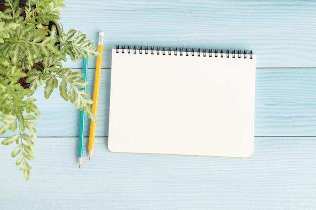 Пустой ноутбук с и карандаш на синем фоне