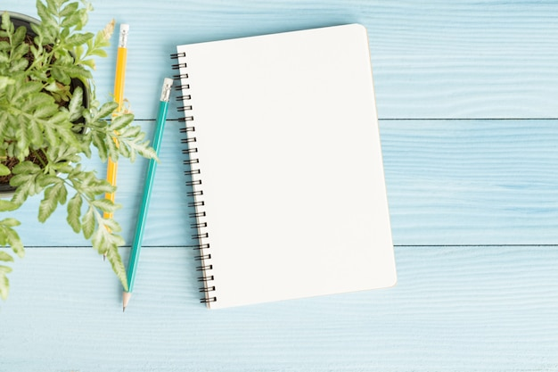Пустой блокнот с карандашом на синем фоне