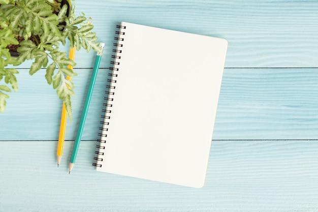 空白のノートブックと青の背景に鉛筆