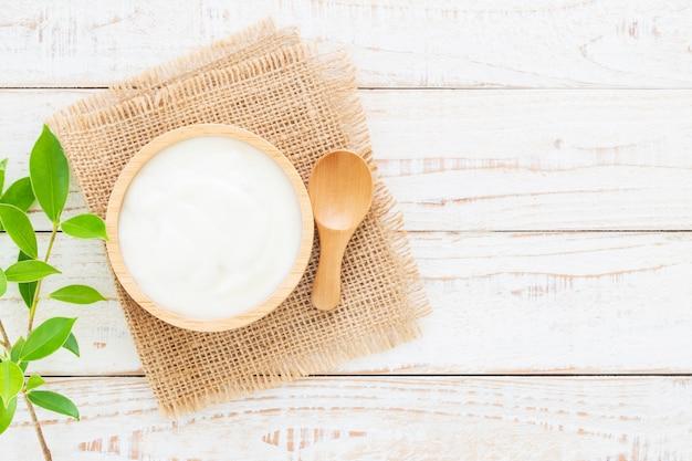 白い木製のテーブルの上の木のボウルにヨーグルト健康食品のコンセプト