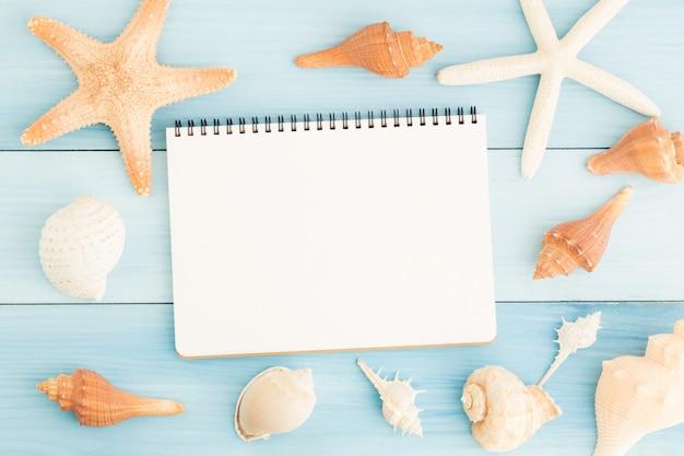 空白のノートブックと青い木製の床の貝殻。