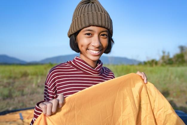 アジアの女の子の笑顔と冬のキャンプで自然を楽しんで幸せ。休日の家族のライフスタイルのコンセプト
