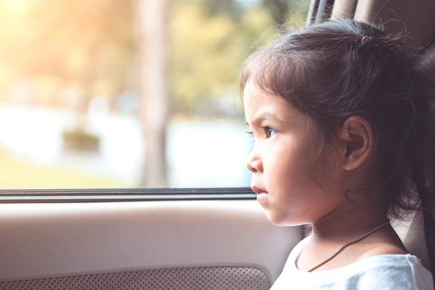 Симпатичные азии маленькая девочка, сидя в машине и смотреть из окна автомобиля на закате
