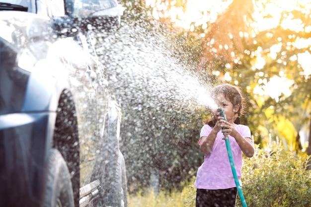 幸せなアジアの子供の女の子の助け親太陽の光と水スプラッシュで車を洗う