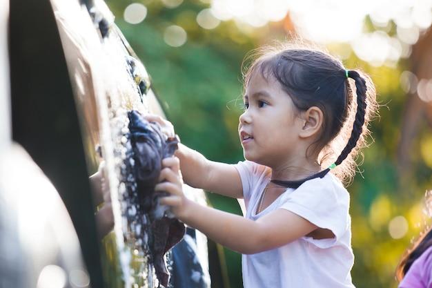太陽の光で親を洗うのを助ける楽しみを持つ、幸せなアジアの子供の女の子