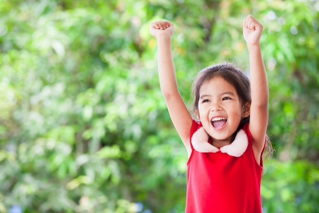 Счастливый азии девочка в рождественские платье, подняв ее руки и кричать с веселой на фоне зеленой природы