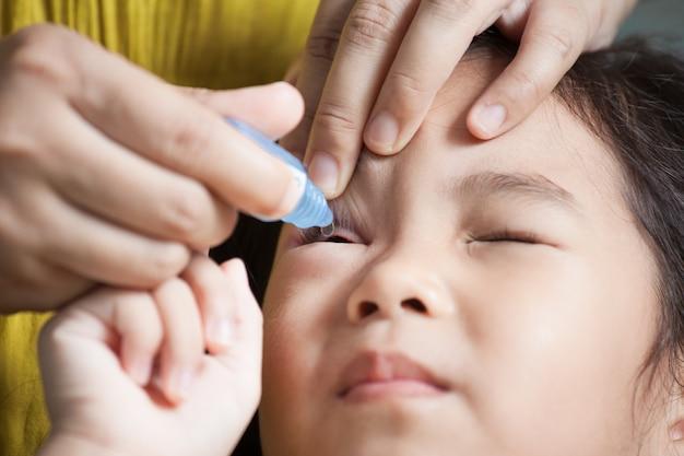 子供の目に眼薬を滴下する母親