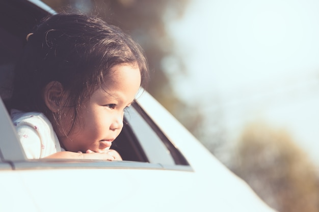 かわいいアジアの小さな子供の女の子車で旅行し、ヴィンテージの色調で田舎の車の窓から見て