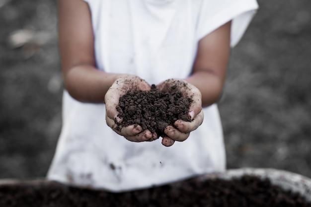 植えるために手に黒い土を持っている小さな子供の女の子