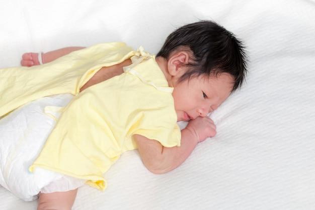 かわいい新生児の少年は彼のベッドの上でうそつきやすい