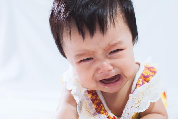 Портрет милой азии девочка плачет в своей спальне с устал перед сном