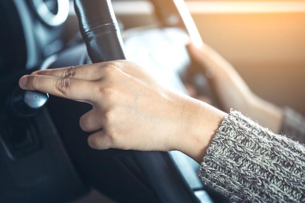 車の運転中に車の雨のフロントガラスのワイパーコントロールスティックを制御する女性の手