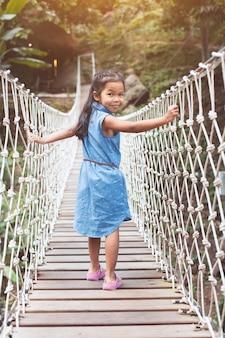 かわいいアジアの子供の女の子は、森の川を渡ってぶら下がっているロープの橋を歩いて