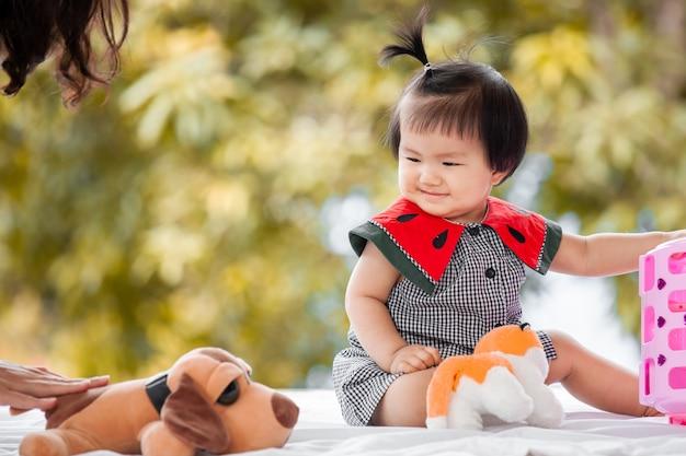 彼女のおもちゃで遊んでいるかわいいアジアの女の子