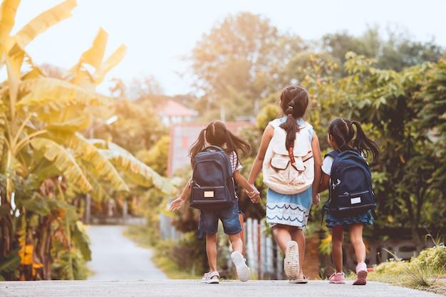 一緒に学校に行くバックパックとアジアの瞳の子供たち