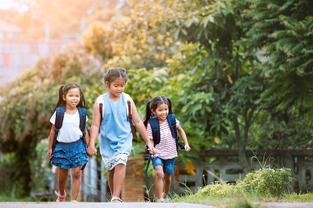 学校に戻る。一緒に学校に行くバックパックとアジアの瞳の子供たち