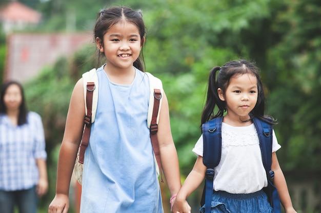 手を持って一緒に学校に行くバックパック付きアジアの瞳の子供たち
