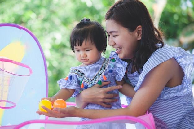 幸せなアジアの母親と一緒に遊ぶかわいい小さな女の子