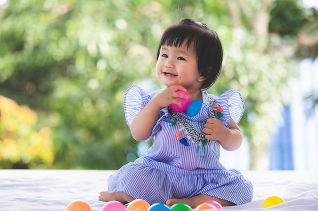 幸せで彼女のおもちゃで遊んでいるかわいいアジアの女の子