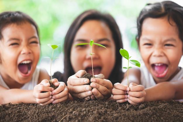 幸せな家族の母親と娘は、植えのために手に若い木を保持するのが楽しい