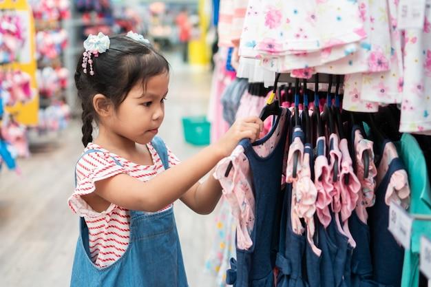 かわいいアジアの子供の女の子がスーパーマーケットの服部門でドレスを選ぶ