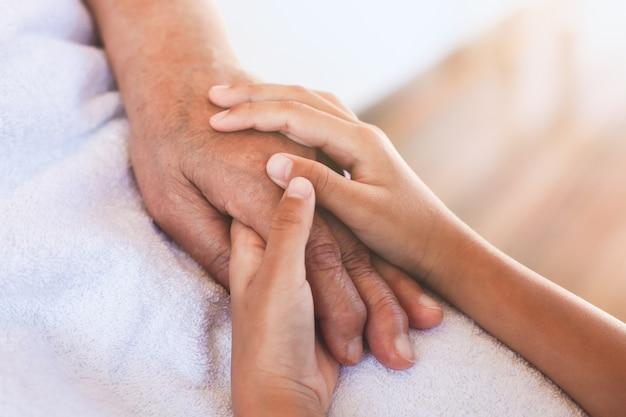 アジアの子供の女の子の手を保持している高齢者の祖父母の手のケアと愛を感じてしわ肌
