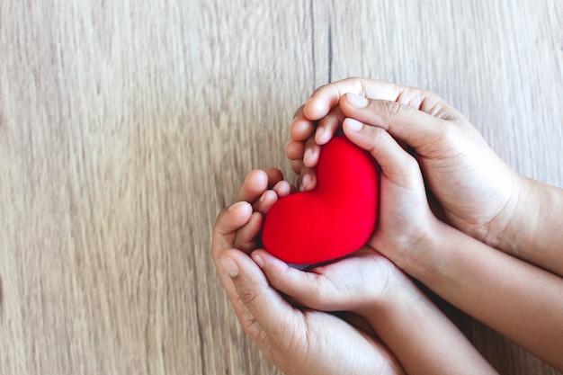 愛と調和を持つ木製のテーブル背景に子供の手と親の手で赤いハート