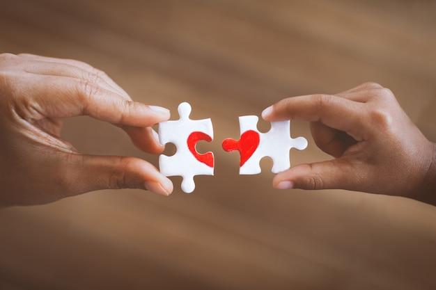 親と子供の手が描かれた赤いハートのカップルジグソーパズルのピースを接続する