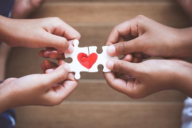 Две детские руки соединяют кусочек головоломки с нарисованным красным сердцем