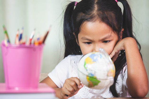かわいいアジアの子供の女の子は教室で地球を見て、勉強するために拡大鏡を使う