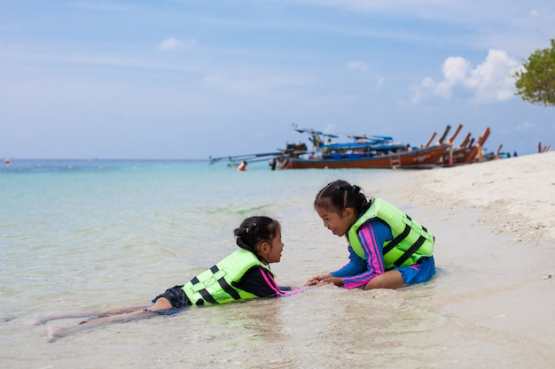 Две милые азиатские девочки в спасательном жилете играют с водой в красивом море вместе с удовольствием