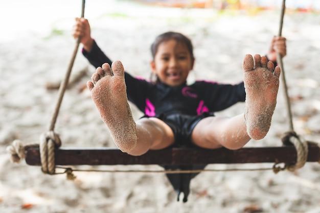 Ребенок ноги с песком, пока она играет на качелях на пляже у моря в летние каникулы