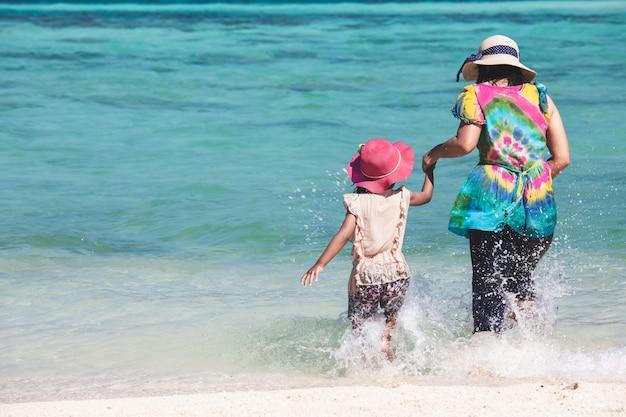 若いアジアの母親とかわいい小さな娘が美しい海で一緒に水を遊ぶ