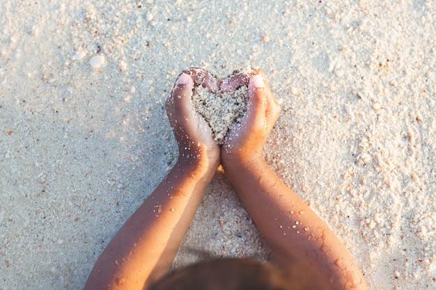 砂を保持している子女の子は手でハートを作ると夏休みにビーチで遊んで