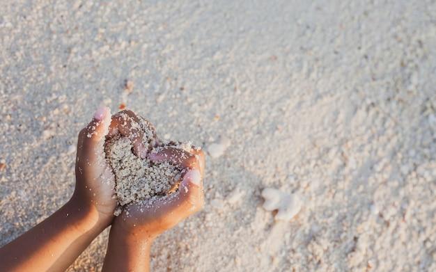 Девушка ребенка держа песок делает форму сердца в руках и играя на пляже в летних каникулах