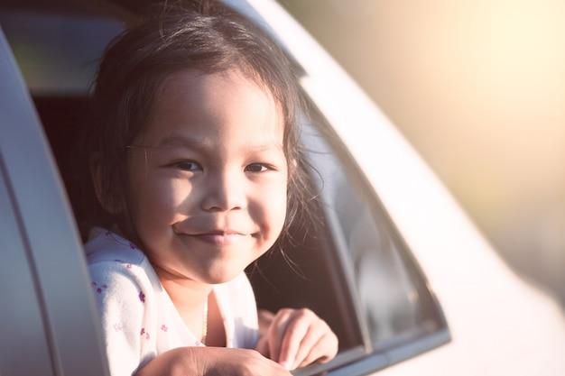 Азиатская маленькая девочка ребенка, улыбаясь и с удовольствием путешествовать на машине и глядя из окна автомобиля
