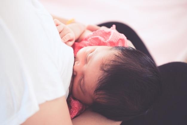 Мать кормит своего новорожденного ребенка девочкой.
