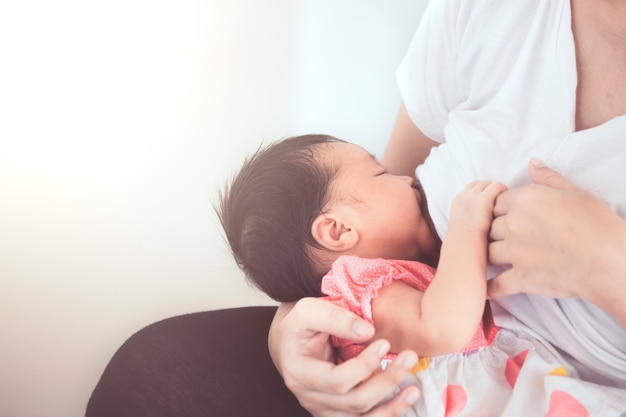 彼女の生まれたばかりの女の赤ちゃんを母乳で育てる母親。