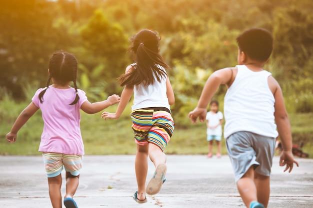 フィールドで一緒に走って遊ぶのが楽しいアジアの子供たちの背面図