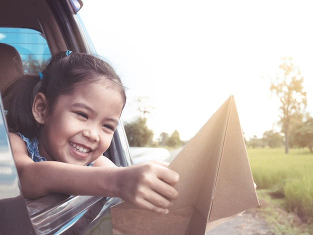 車の窓の外のおもちゃの紙飛行機で遊ぶことを楽しんでいるかわいいアジアの小さな子女の子