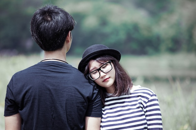 Азиатская молодая женщина отдыхает на плече своего парня с любовью снаружи