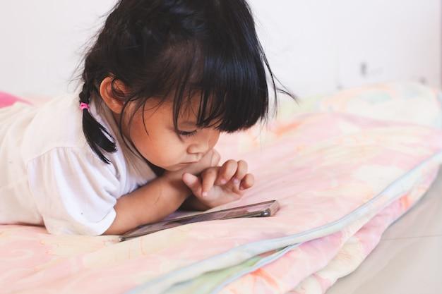 彼女の部屋で彼女のベッドに横になっているスマートフォンを弾くかわいいアジアの赤ちゃん女の子