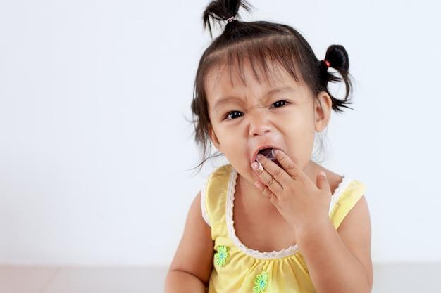 Девушка ребенка милого младенца азиатская есть лапшу сама и делая беспорядок на ее лице и руке