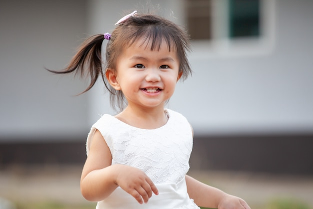 笑顔で楽しさと幸福を持って走っているかわいいアジアの女の子